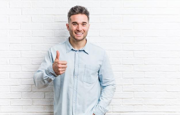 Młody przystojny mężczyzna uśmiecha się i podnosząc kciuk o ścianę cegieł