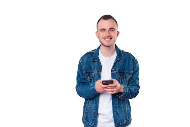 Młody przystojny mężczyzna uśmiecha się i używa smartfona