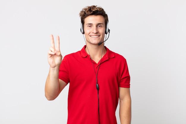 Młody przystojny mężczyzna uśmiecha się i wygląda na szczęśliwego, gestykulując zwycięstwo lub pokój. koncepcja telemarketera