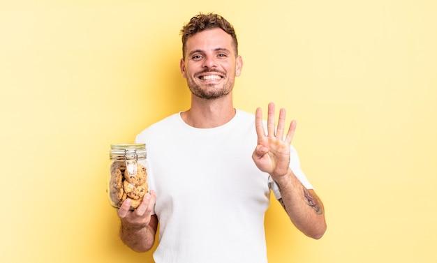 Młody przystojny mężczyzna uśmiecha się i wygląda przyjaźnie, pokazując koncepcję butelki ciasteczek numer cztery