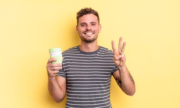 Młody przystojny mężczyzna uśmiecha się i wygląda przyjaźnie, pokazując koncepcję numer trzy na wynos
