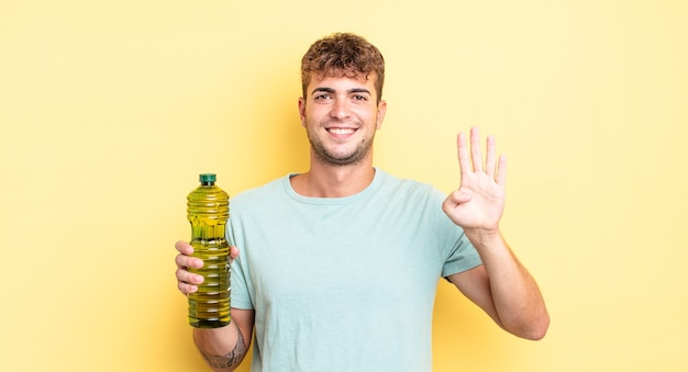 Młody przystojny mężczyzna uśmiecha się i wygląda przyjaźnie, pokazując numer cztery. koncepcja oliwy z oliwek