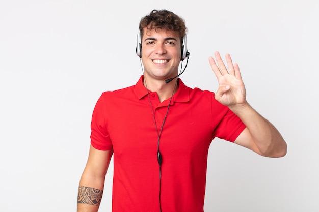 Młody przystojny mężczyzna uśmiecha się i wygląda przyjaźnie, pokazując numer cztery. koncepcja telemarketera