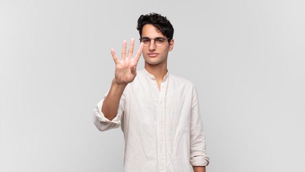 Młody przystojny mężczyzna uśmiecha się i wygląda przyjaźnie, pokazując numer cztery lub czwarty z ręką do przodu