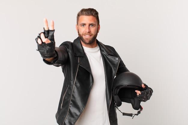 Młody przystojny mężczyzna uśmiecha się i wygląda przyjaźnie, pokazując numer dwa. koncepcja kasku motocyklowego