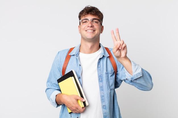 Młody przystojny mężczyzna uśmiecha się i wygląda przyjaźnie, pokazując numer dwa. koncepcja studenta uniwersytetu