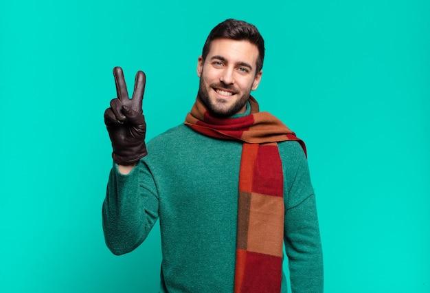 Młody przystojny mężczyzna uśmiecha się i wygląda przyjaźnie, pokazując numer dwa lub drugi z ręką do przodu, odliczając w dół