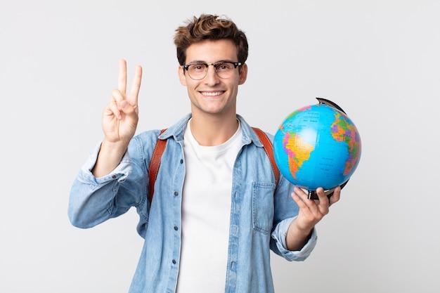 Młody przystojny mężczyzna uśmiecha się i wygląda przyjaźnie, pokazując numer dwa. student trzymający mapę kuli ziemskiej