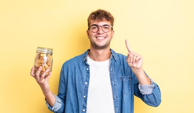 Młody przystojny mężczyzna uśmiecha się i wygląda przyjaźnie, pokazując numer jeden. koncepcja butelki ciasteczek