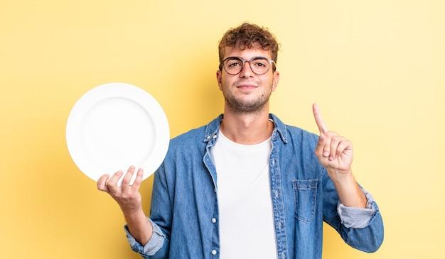 Młody przystojny mężczyzna uśmiecha się i wygląda przyjaźnie, pokazując numer jeden. koncepcja pustego naczynia