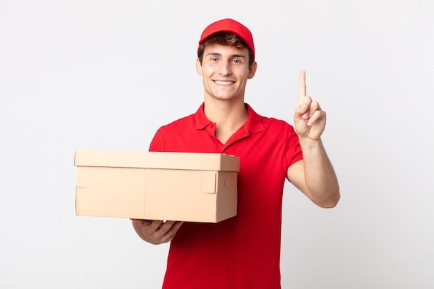 Młody przystojny mężczyzna uśmiecha się i wygląda przyjaźnie, pokazując numer jeden koncepcja usługi pakietu dostawy.