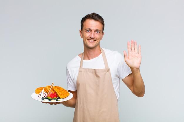 Młody przystojny mężczyzna uśmiecha się i wygląda przyjaźnie, pokazując numer jeden lub pierwszy z ręką do przodu, odliczając