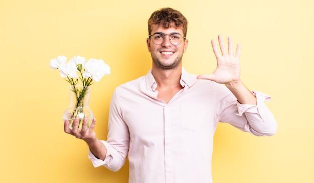 Młody przystojny mężczyzna uśmiecha się i wygląda przyjaźnie, pokazując numer pięć. koncepcja kwiaty