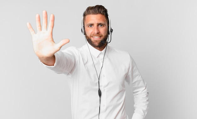 Młody przystojny mężczyzna uśmiecha się i wygląda przyjaźnie, pokazując numer pięć. koncepcja telemarketingu
