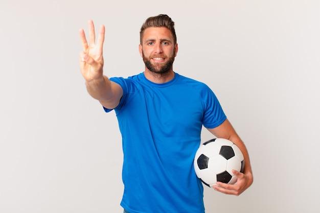 Młody przystojny mężczyzna uśmiecha się i wygląda przyjaźnie, pokazując numer trzy. koncepcja piłki nożnej