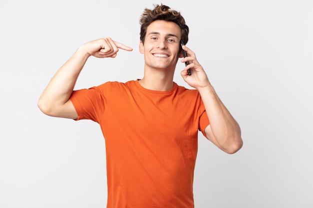 Młody przystojny mężczyzna uśmiecha się pewnie, wskazując na swój szeroki uśmiech i rozmawia ze smartfonem