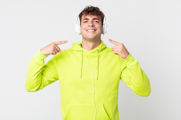 Młody przystojny mężczyzna uśmiecha się pewnie wskazując na swój szeroki uśmiech i słuchawki