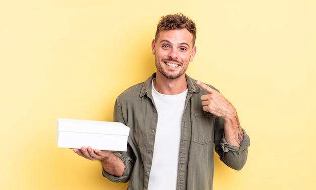 Młody przystojny mężczyzna uśmiecha się pewnie wskazując na własny szeroki uśmiech. koncepcja białego pudełka