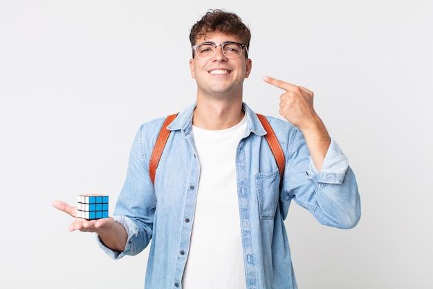 Młody przystojny mężczyzna uśmiecha się pewnie wskazując na własny szeroki uśmiech. koncepcja gry wywiadowczej