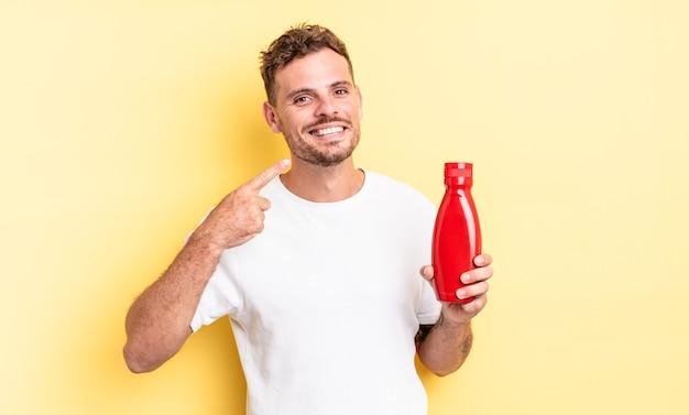 Młody przystojny mężczyzna uśmiecha się pewnie wskazując na własny szeroki uśmiech. koncepcja ketchupu