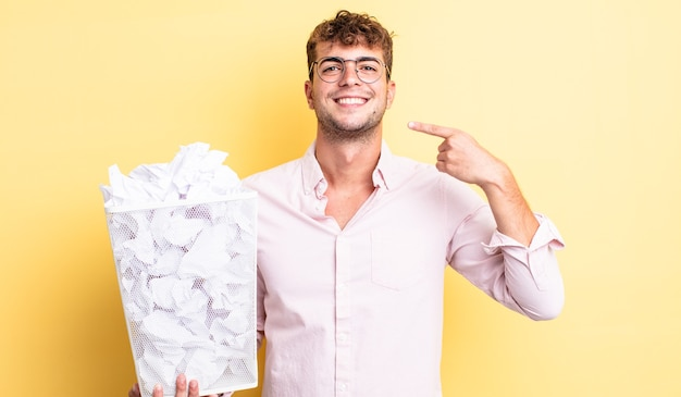 Młody przystojny mężczyzna uśmiecha się pewnie wskazując na własny szeroki uśmiech. koncepcja śmieci z kulkami papierowymi