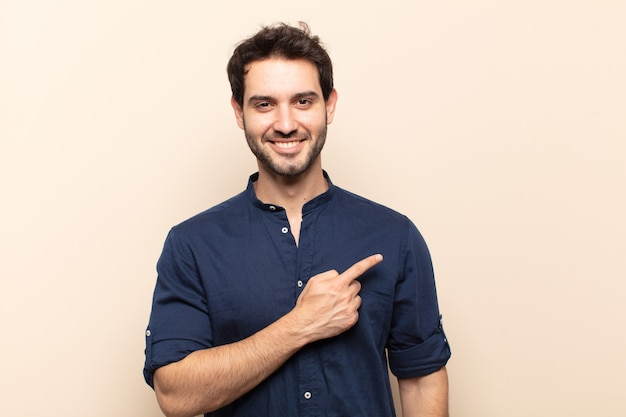 Młody przystojny mężczyzna uśmiecha się radośnie, czuje się szczęśliwy i wskazuje na bok i do góry, pokazując obiekt w przestrzeni kopii