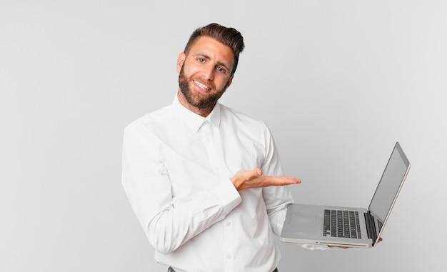 Młody przystojny mężczyzna uśmiecha się radośnie, czuje się szczęśliwy, pokazuje koncepcję i trzyma laptopa