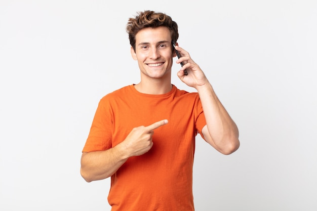 Młody przystojny mężczyzna uśmiecha się radośnie, czuje się szczęśliwy, wskazuje na bok i rozmawia ze smartfonem