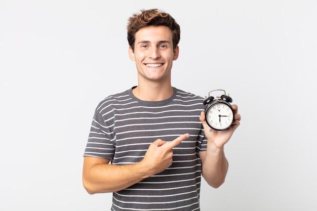 Młody przystojny mężczyzna uśmiecha się radośnie, czuje się szczęśliwy, wskazuje na bok i trzyma budzik