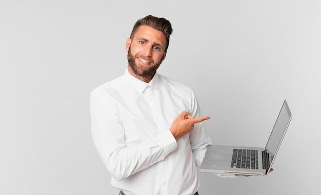 Młody przystojny mężczyzna uśmiecha się radośnie, czuje się szczęśliwy, wskazuje na bok i trzyma laptopa