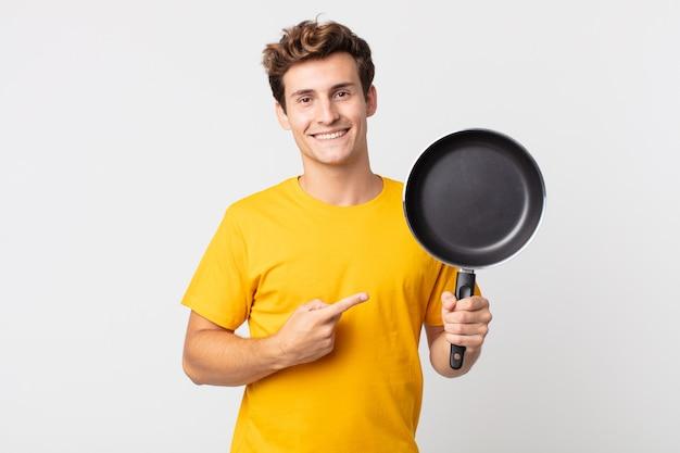 Młody przystojny mężczyzna uśmiecha się radośnie, czuje się szczęśliwy, wskazuje na bok i trzyma patelnię kucharską