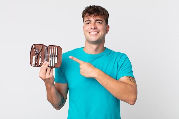 Młody przystojny mężczyzna uśmiecha się radośnie, czuje się szczęśliwy, wskazuje na bok i trzyma walizkę z narzędziami do paznokci