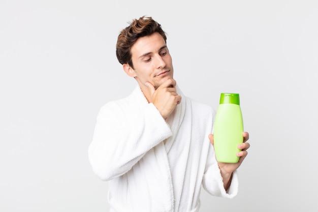Młody przystojny mężczyzna uśmiecha się radośnie i marzy lub wątpi w szlafrok i trzyma butelkę szamponu