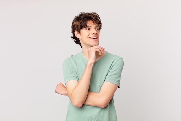 Młody przystojny mężczyzna uśmiecha się radośnie i marzy lub wątpi