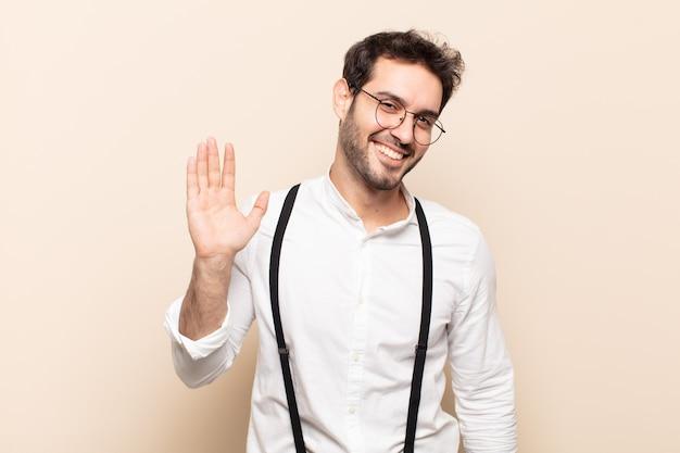 Młody Przystojny Mężczyzna Uśmiecha Się Radośnie I Wesoło, Macha Ręką, Wita I Wita Lub żegna Się Premium Zdjęcia