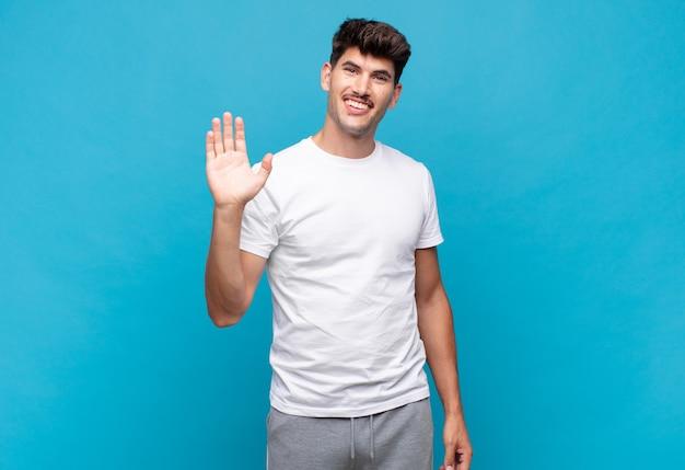 Młody przystojny mężczyzna uśmiecha się radośnie i wesoło, macha ręką, wita i wita lub żegna się