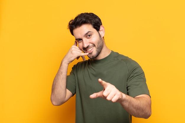 Młody przystojny mężczyzna uśmiecha się radośnie i wskazuje podczas wykonywania połączenia później gestu, rozmawia przez telefon