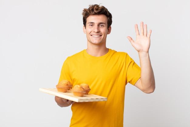 Młody przystojny mężczyzna uśmiecha się radośnie, macha ręką, wita cię i wita cię, trzymając tacę z babeczkami