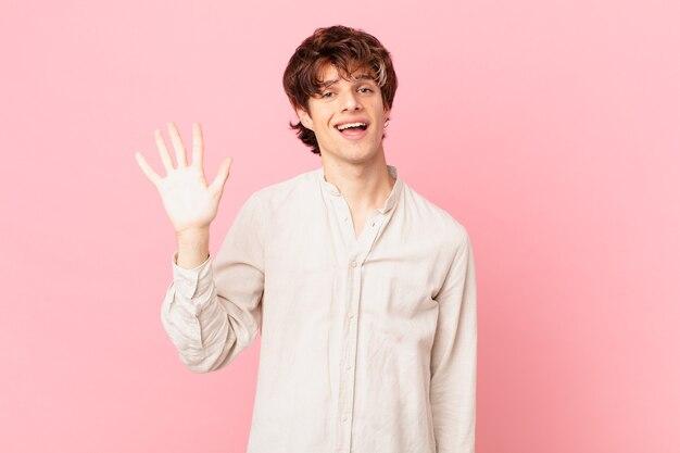 Młody przystojny mężczyzna uśmiecha się radośnie, macha ręką, wita cię i wita greeting