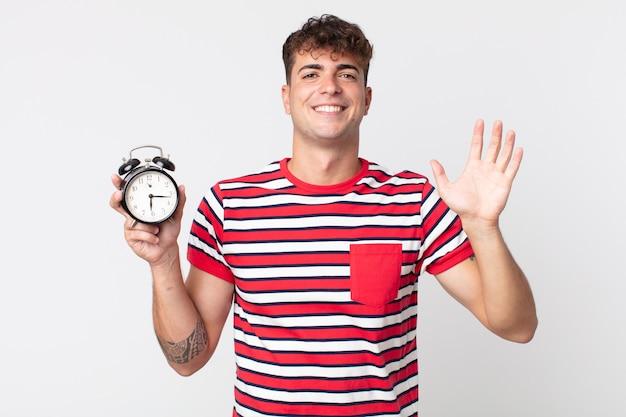 Młody przystojny mężczyzna uśmiecha się radośnie, macha ręką, wita cię i wita i trzyma budzik