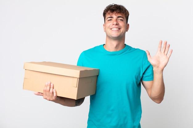 Młody przystojny mężczyzna uśmiecha się radośnie, macha ręką, wita cię i wita i trzyma kartonowe pudełko