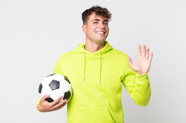 Młody przystojny mężczyzna uśmiecha się radośnie, macha ręką, wita cię i wita i trzyma piłkę nożną