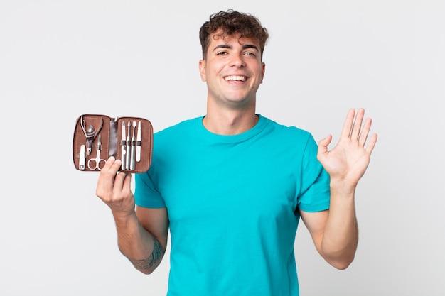 Młody przystojny mężczyzna uśmiecha się radośnie, macha ręką, wita cię i wita i trzyma walizkę z narzędziami do paznokci