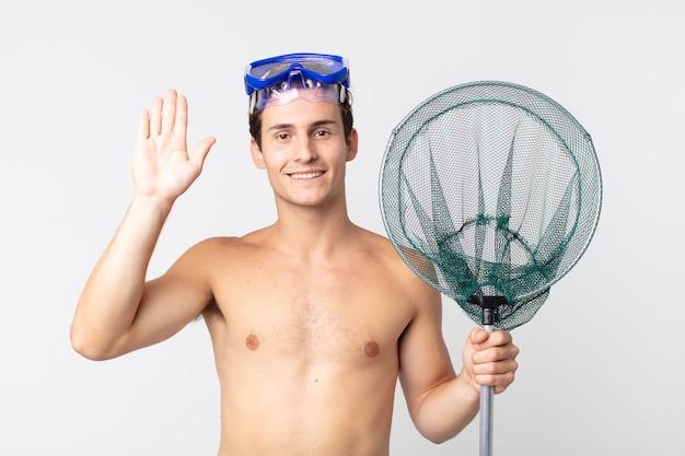 Młody przystojny mężczyzna uśmiecha się radośnie, macha ręką, wita i wita cię goglami i siecią rybacką