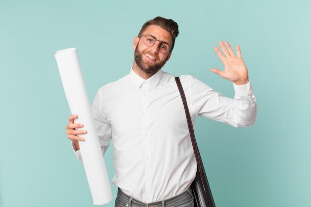 Młody przystojny mężczyzna uśmiecha się radośnie, machając ręką, witając cię i pozdrawiając. koncepcja architekta