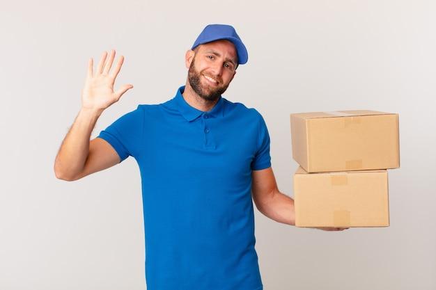 Młody przystojny mężczyzna uśmiecha się radośnie, machając ręką, witając cię i pozdrawiając. koncepcja dostarczania paczek