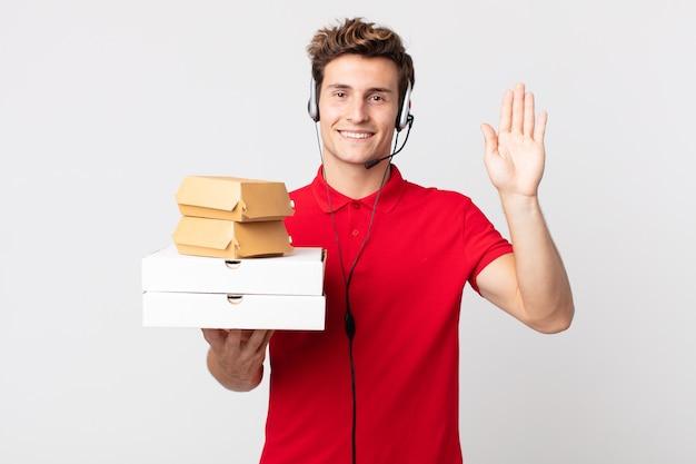 Młody przystojny mężczyzna uśmiecha się radośnie, machając ręką, witając cię i pozdrawiając. koncepcja fast foodów na wynos