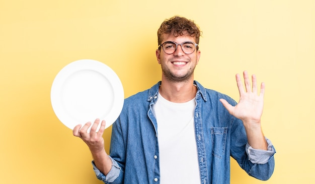 Młody przystojny mężczyzna uśmiecha się radośnie, machając ręką, witając cię i pozdrawiając. koncepcja pustego naczynia