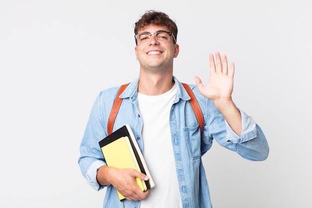Młody przystojny mężczyzna uśmiecha się radośnie, machając ręką, witając cię i pozdrawiając. koncepcja studenta uniwersyteckiego