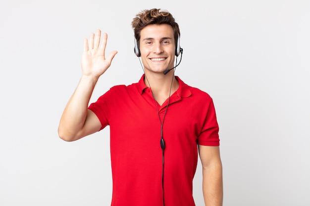 Młody przystojny mężczyzna uśmiecha się radośnie, machając ręką, witając cię i pozdrawiając. koncepcja telemarketera